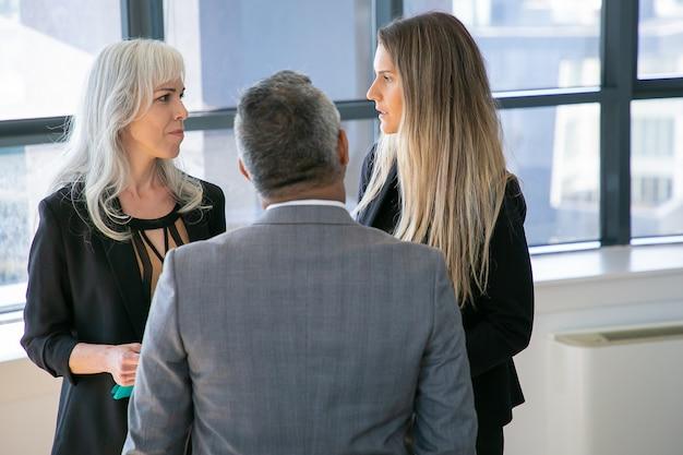男性の上司と話し、オフィスに立ち、プロジェクトについて話し合う女性マネージャー。ミディアムショット、背面図。ビジネスコミュニケーションまたはブリーフィングの概念