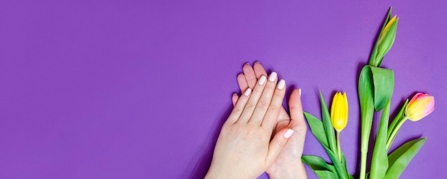Female manicure on a bright background. purple background with flowers. banner.