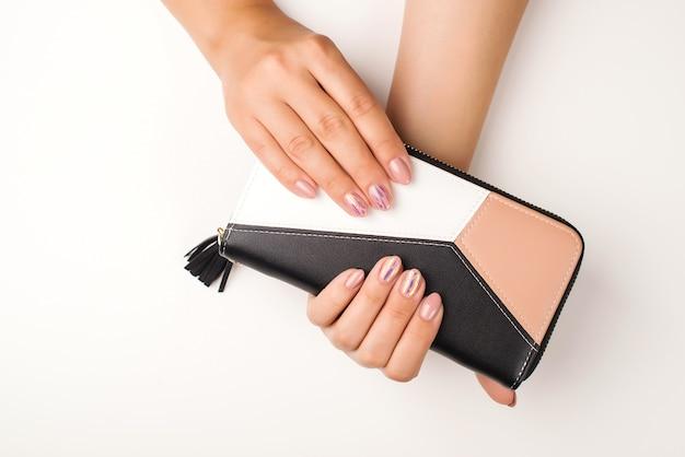Женский маникюр руками. мода молодая женщина руки держит кошелек. женские руки, вид сверху.