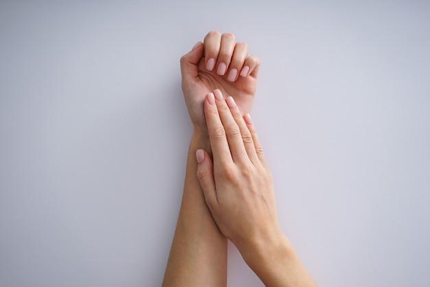 여성 매니큐어. 회색 바탕에 아름 다운 매니큐어와 젊은 여자의 손. 평평하다.
