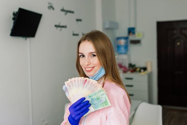 Мастер женского маникюра в салоне красоты с защитной маской, держащей деньги и улыбающейся