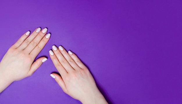 明るい背景の女性のマニキュア。紫の背景。バナー。