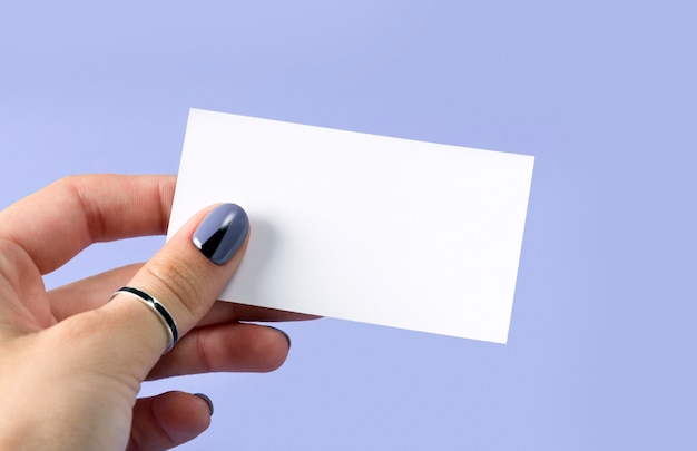 Female manicured hand holding a blank business card