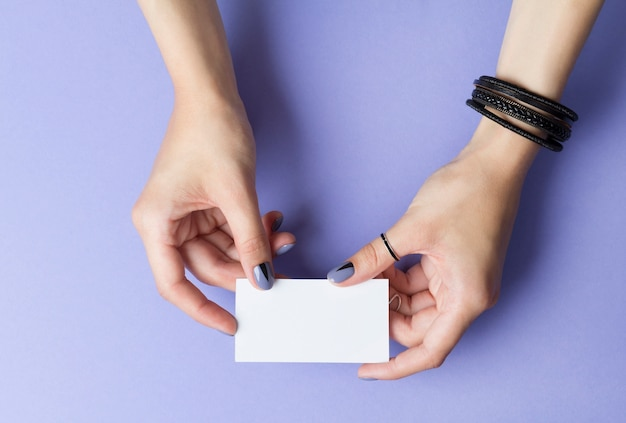 Female manicured hands holding a blank business card