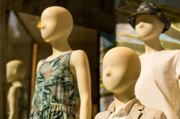 Female mannequins in dresses in th storefront