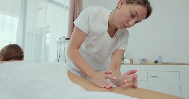 바디, 다리 및 발 마사지 및 림프 배수를 만드는 여성 마사지. 뷰티 스파 살롱에서 안티 셀룰라이트 마사지를 받는 젊은 여성. 미용실에서 마사지 치료사.