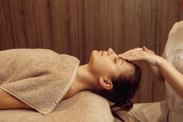 Женский массажист трет лицо молодой стройной женщины в полотенце, профессиональный массаж. массаж и расслабление, уход за телом и кожей. привлекательная дама в спа-салоне