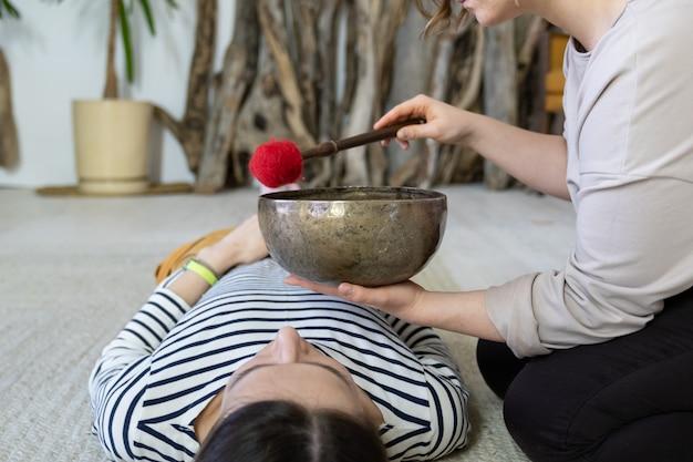 여성 마사지는 편안한 여자에서 전통적인 티베트어 사운드 테라피 노래 그릇 마사지를 수행
