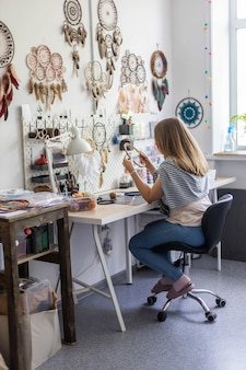 Female master creating dreamcatcher working at workshop with feathers and materials