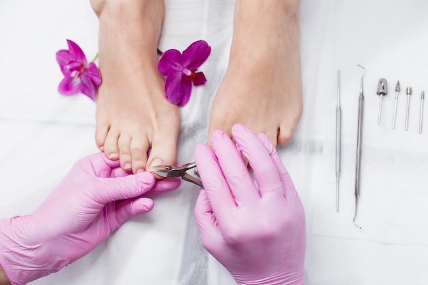 Женщина мастер делает педикюр с клиентом в салоне красоты