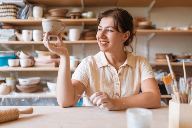 Мастерица держит свежий расписной горшок, гончарную мастерскую. женщина лепит миску.