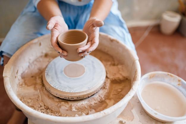 女性のマスターは、ろくろの上に濡れた鍋を持っています。