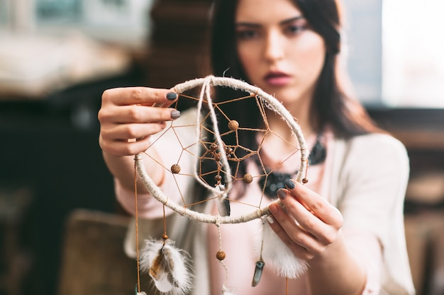 Female master looking on finished dreamcatcher