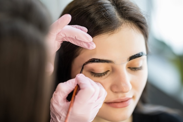 Female master make contours of eyebrows for pretty young model
