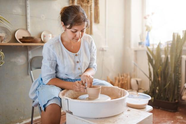 Female master making a pot on pottery wheel. woman molding a bowl.