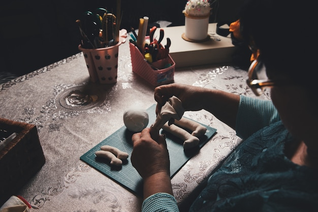 Female master making sculpture from clay