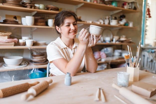 女性のマスターが鉢、陶器の工房を描きます。