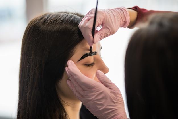 Female master in white gloves determine eyebrow contour