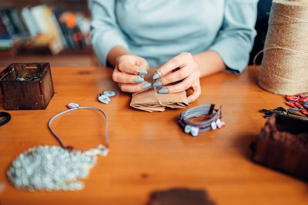 Мастерица с ножницами делает серьгу ручной работы