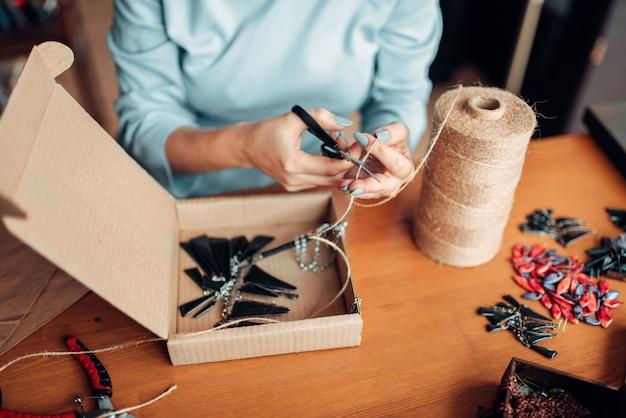 Мастерица с ножницами делает серьги ручной работы