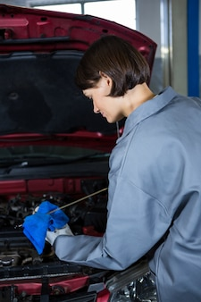 Female mechanic checking the oil level in a car engine