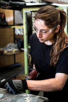 Женщина-механик сверлит металл