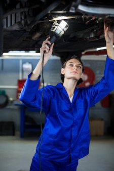 ランプが付いている車を調べる女性メカニック