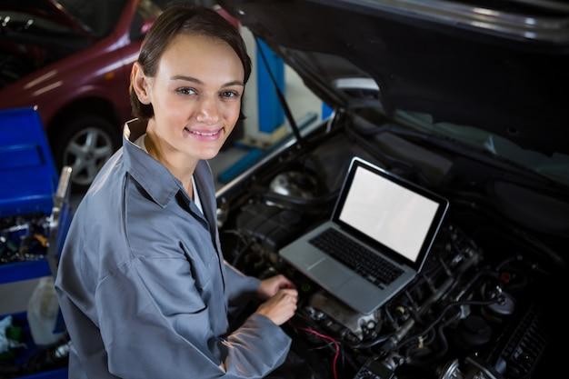 Female mechanic examining car engine with help of laptop