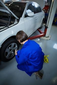 공 압 렌치와 자동차 바퀴를 고정하는 여성 정비공