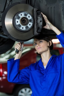 Female mechanic fixing a car wheel disc brake