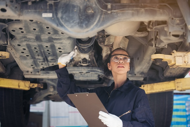 Female mechanic inspecting a lifted car