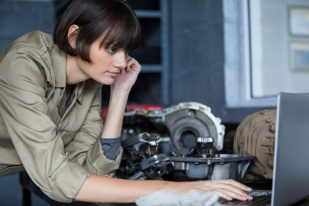Женщина механик, опираясь на стол и с помощью ноутбука