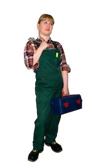Female mechanic or plumber in bib overalls with adjustable wrench and toolbox looking up