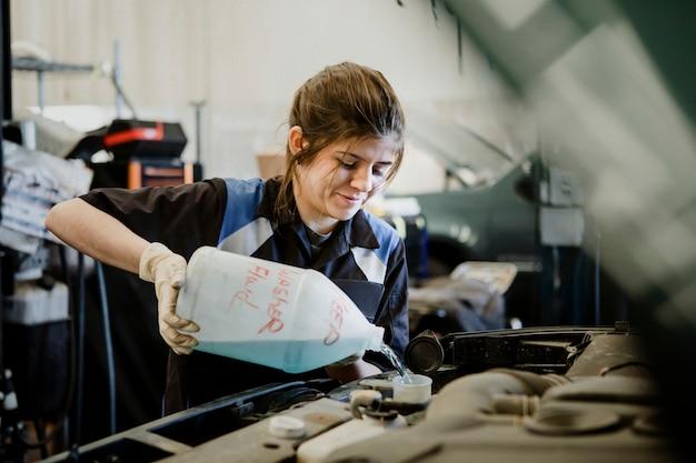 Женщина-механик наливает воду в радиатор