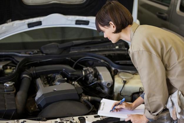 Female mechanic preparing a check list