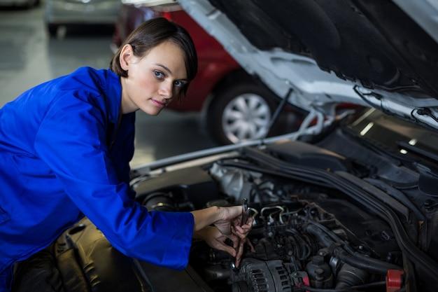 車にサービスを提供する女性メカニック