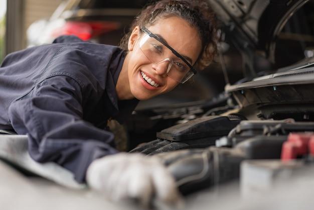 여성 정비공 미소 및 자동 서비스 차고에서 자동차 수리 유지 보수 작업