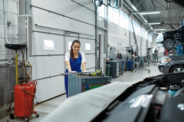여성 정비공은 후드, 자동차 서비스에 선다. 차량 수리 차고, 여자 유니폼, 자동차 역 내부