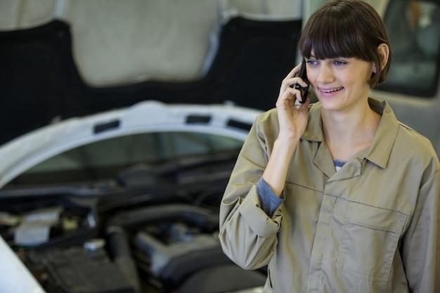 Meccanico femminile parlando di un telefono cellulare