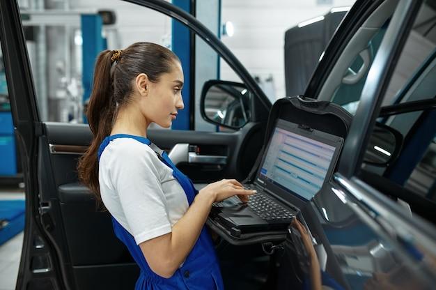노트북이 있는 여성 정비사는 엔진 진단, 자동차 서비스, 전문 검사를 합니다