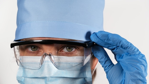 Female medic in disposable medical mask, protective plastic glasses and textile cap, portrait of a tired doctor with sad eyes, close up