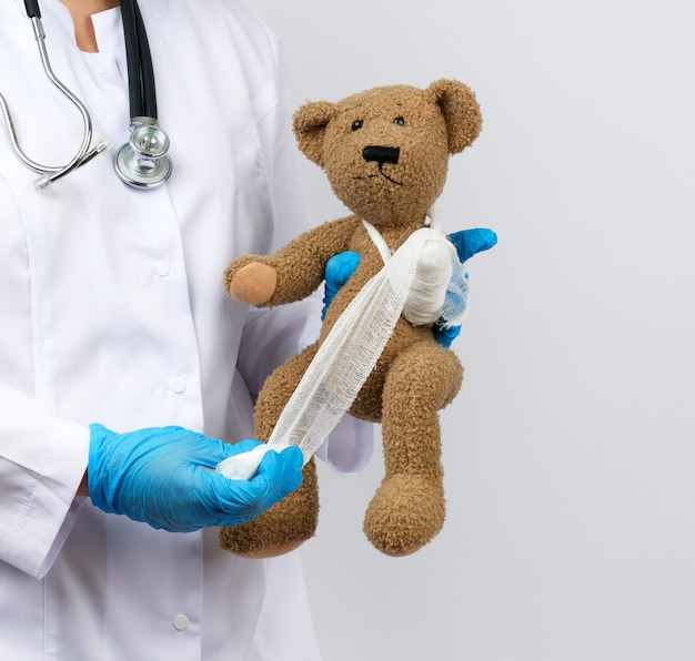 Female medic holds brown teddy bear and bandages paw with white gauze bandage