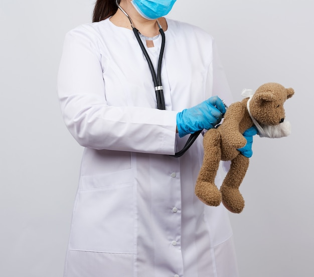 Female medic holds brown teddy bear with paw bandaged in white bandage and listens to toy with stethoscope