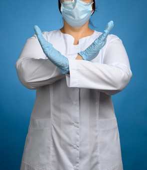 Female medic in a white coat, a mask stands on a blue background, arms crossed, a gesture enough