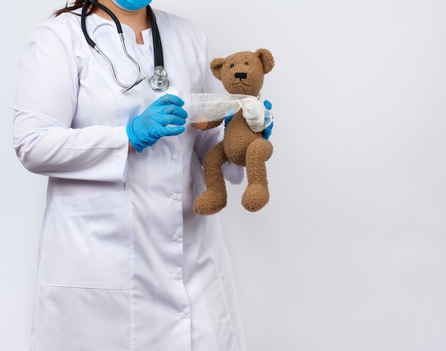 Female medic in a white coat with buttons holding a brown teddy bear and bandaging her paw