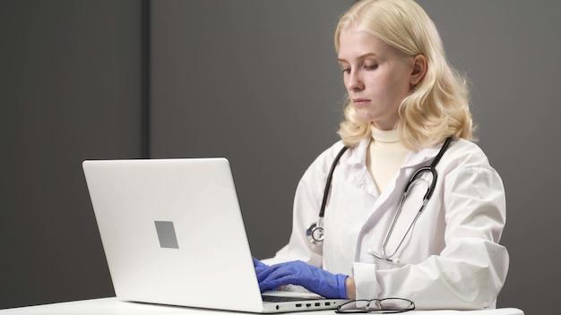 여성 의료 보조원은 노트북에 먼 환자를 호출하는 흰색 코트, 헤드셋 비디오를 착용합니다. 가상 채팅 컴퓨터 앱을 사용하여 클라이언트와 이야기하는 의사. 원격 의료, 원격 의료 서비스 개념.