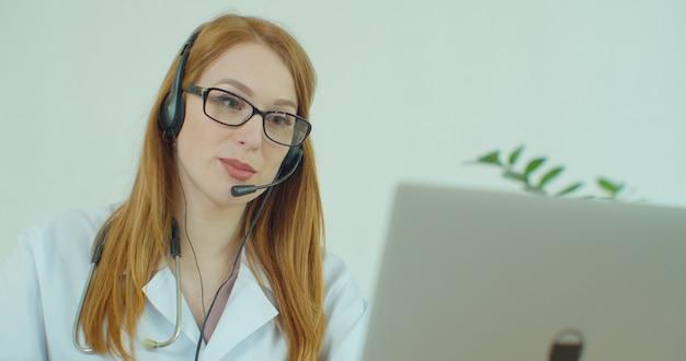 Женский фельдшер носит белое пальто, гарнитура видеозвонка удаленному пациенту на ноутбуке.