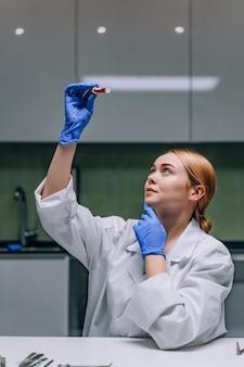 실험실에서 테스트 튜브를보고 여성 의료 또는 과학 연구원.