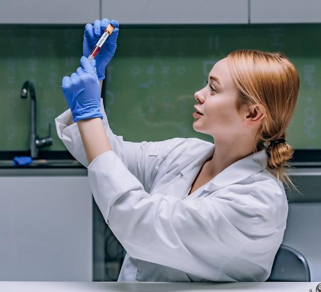 Женский медицинский или научный исследователь, глядя на пробирку в лаборатории.