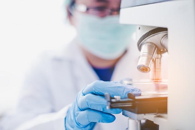 Женский медицинский исследователь, глядя на микроскоп в медицинской лаборатории. медицинская экспериментальная концепция